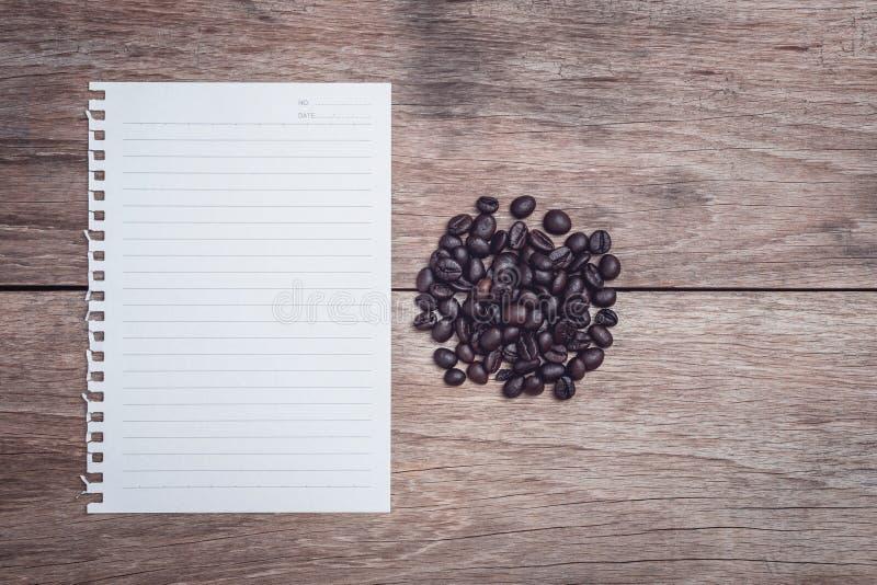 Granos de café y y documento alineado sobre la opinión de sobremesa de madera foto de archivo