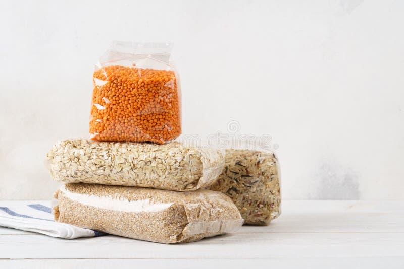Granos de diverso cereal, avenas mondadas en las bolsas de plástico transparentes imagen de archivo