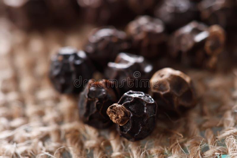 Granos de pimienta negros en un fondo de la arpillera imagen de archivo