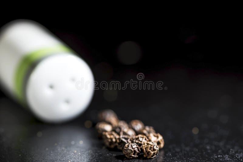 Granos de pimienta negros enteros y coctelera de sal blanca en un fondo negro, aislado fotos de archivo