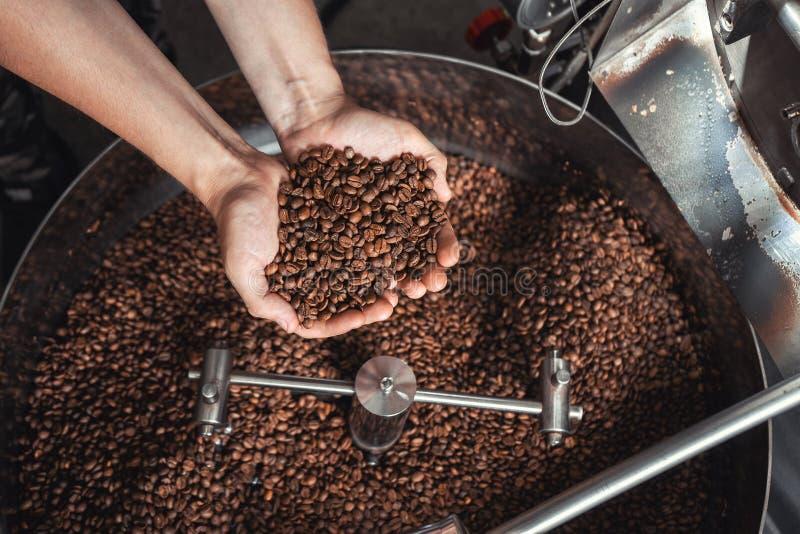 Granos del café fresco que asan en manos en el fondo del asador imagenes de archivo