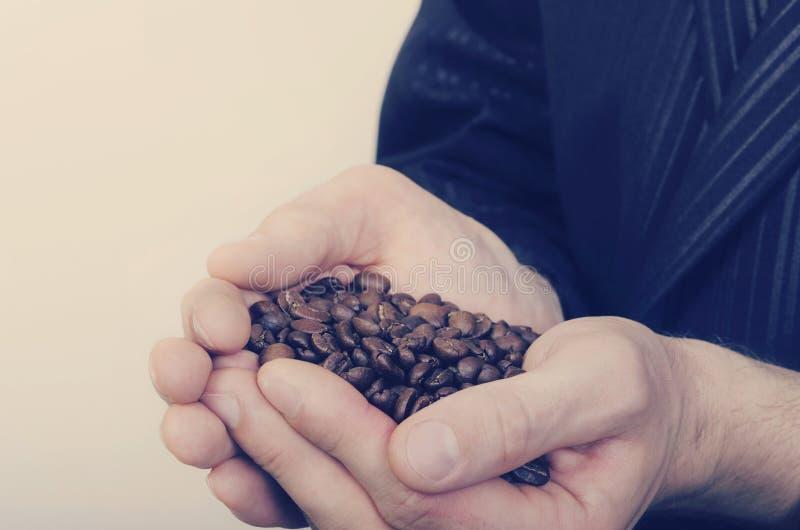 Granos del café sólo en las manos masculinas imagenes de archivo