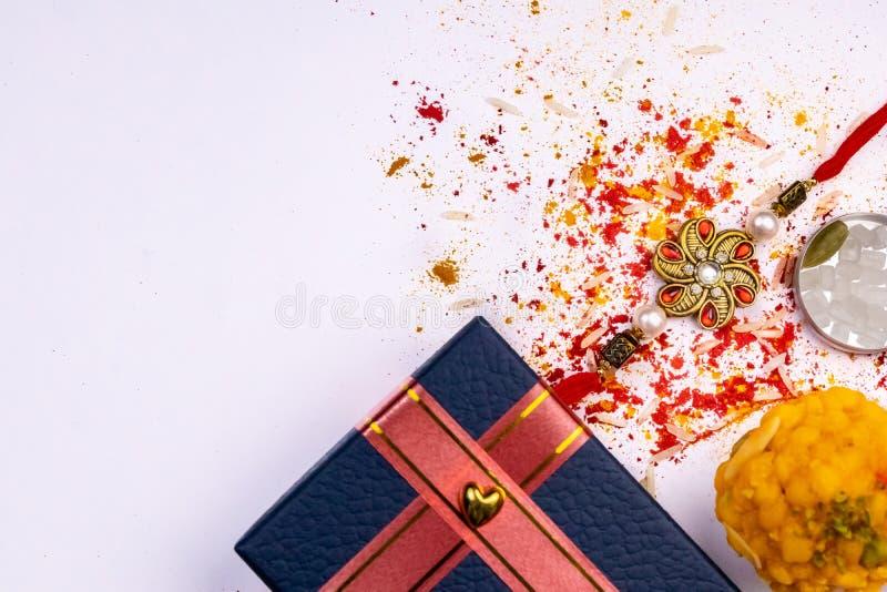 Granos dispersados del arroz, kumkum, haldi, dulces con el cardamomo, azúcar del cristal de roca y caja de regalo azul en el fond imagen de archivo libre de regalías