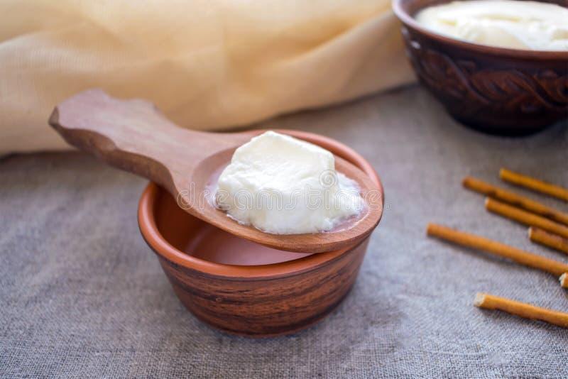 Granos hechos en casa del kéfir de la leche en una cuchara de madera sobre un cuenco o de la arcilla foto de archivo libre de regalías