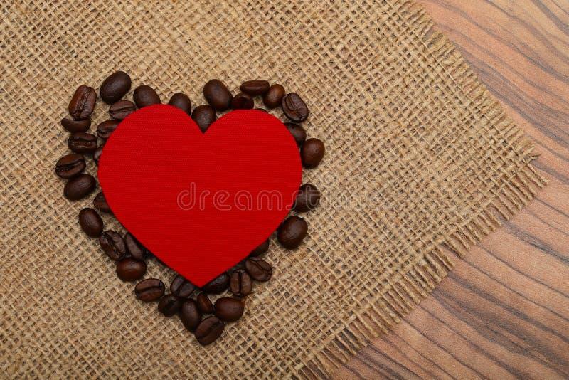 Granos rojos del corazón y de café en una servilleta de la arpillera natural en la tabla fotos de archivo libres de regalías