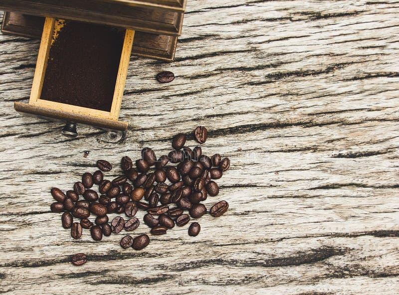 Granos y amoladoras de café en los viejos tableros de madera fotografía de archivo libre de regalías