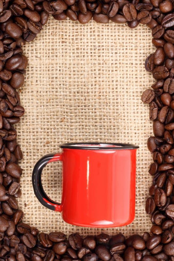 Granos y taza de café en el saco sizal imagen de archivo