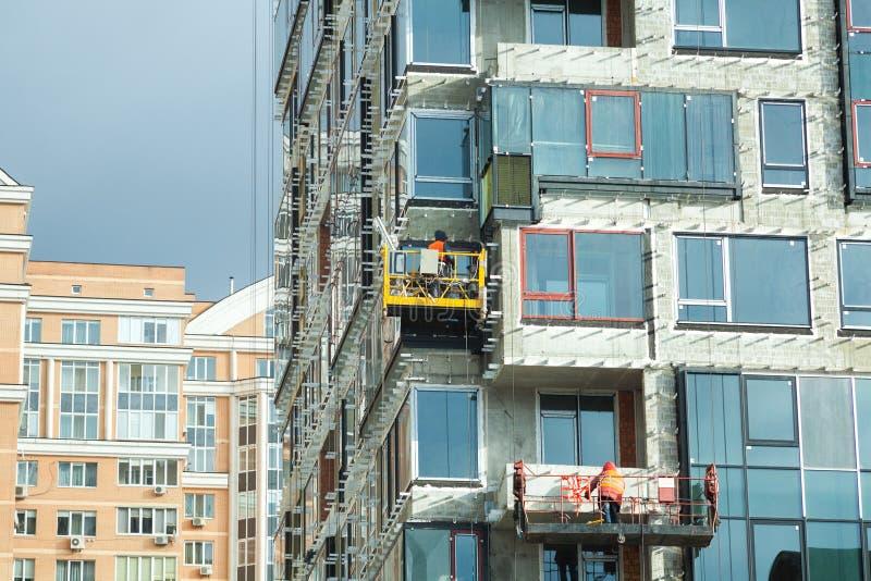 Granskande stor byggnadsplats Arbetare som bygger det nya huset, installerar Windows, väggisolering, balkong Industribyggnad Cons royaltyfri foto