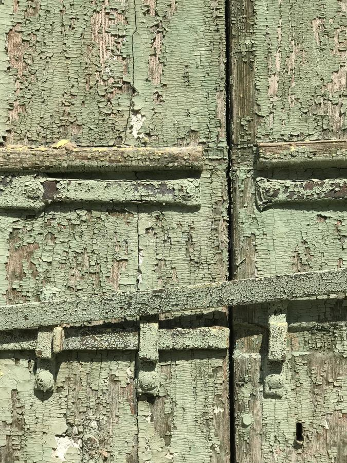 Granular texture of terrific army green chipped paint and a handle on an old door in sun. This is a great piece for a texture artist. A texture artist is an royalty free stock image