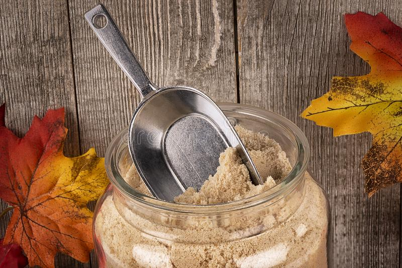 Granulated maple sugar in a jar of glass. stock images