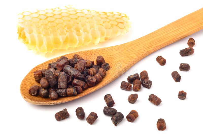 Granules of bee bread in a wooden spoon and a honeycomb are isolated on a white background. Apitherapy. Beekeeping stock photos