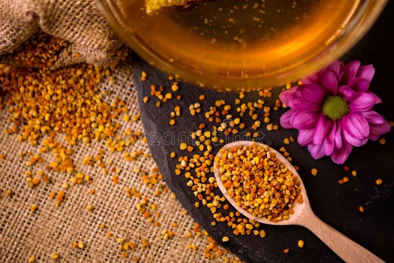 Granules et propolis de pollen d'abeille dans la cuillère en bois photographie stock