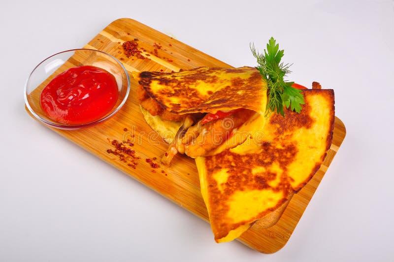 Granulez la tortilla avec le poulet et les légumes sur le conseil en bois photos stock