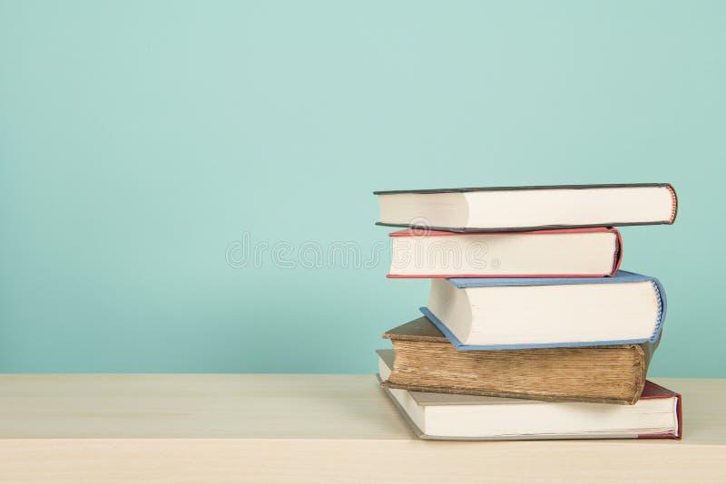 Grapa de 5 libros que se acuestan en un estante de madera en un fondo azul fotos de archivo