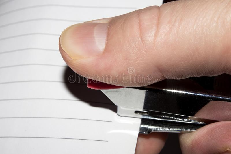 Grapadora a disposición Papel que sujeta con grapa con las grapas imagen de archivo