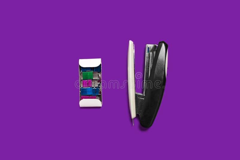 Grapadora negra con la caja de apoyos en una superficie púrpura imágenes de archivo libres de regalías