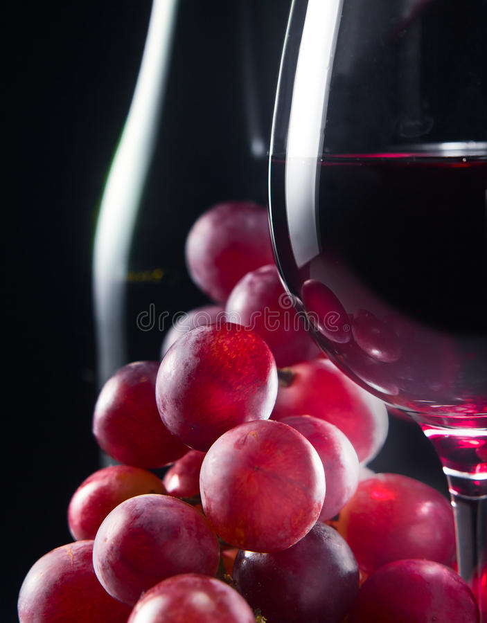 Grape and glass with red wine stock image
