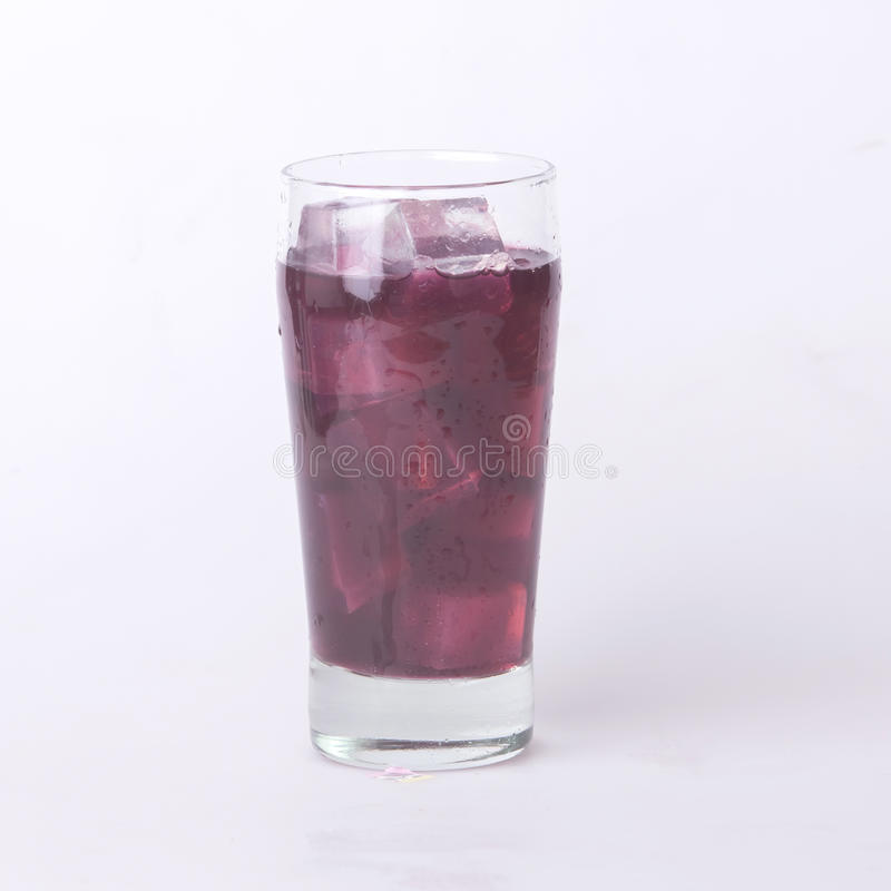 Grape juice in a glass with ice. Juice in wine glasses with ice on the white background royalty free stock image