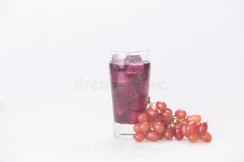 Grape juice in a glass with ice. Juice in wine glasses with ice on the white background royalty free stock photo