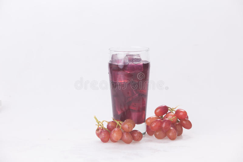 Grape juice in a glass with ice. Juice in wine glasses with ice on the white background stock photo