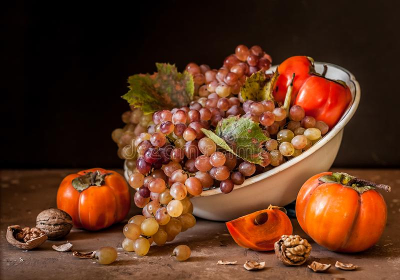 Grape, Persimmon and Walnut Still Life. Harvest Grape, Persimmon and Walnut Still Life stock photos
