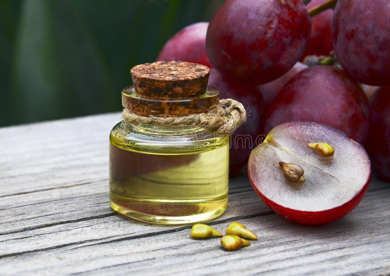 Grape seed oil in a glass jar and fresh grapes on old wooden table. Bottle of organic grape seed oil for spa and bodycare. royalty free stock image