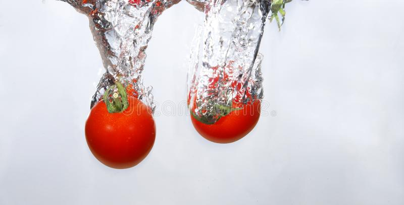 Grape tomatoes into the water stock image