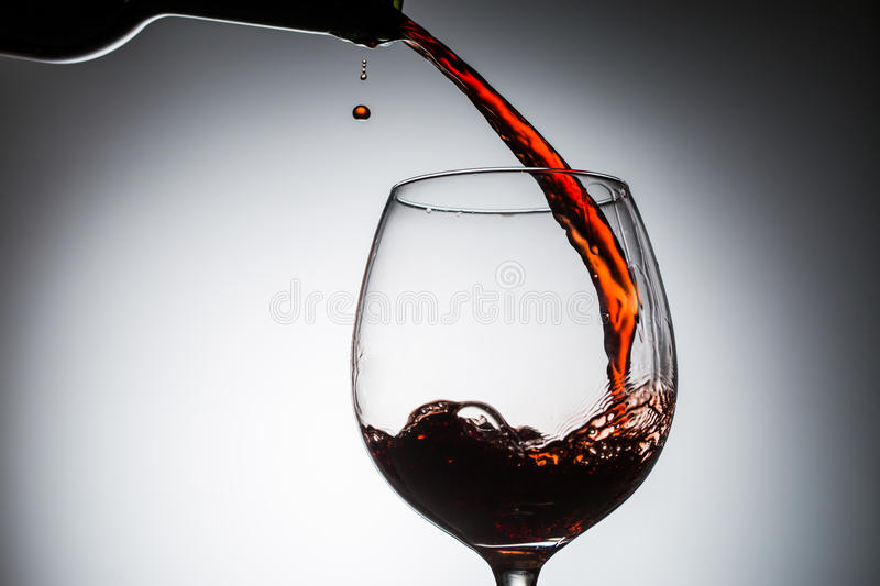 Grape wine poured from bottle into wine glass from glass. On blank background stock photography