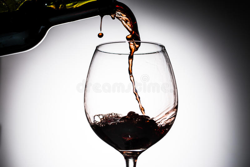 Grape wine poured from bottle into wine glass from glass. On blank background royalty free stock images
