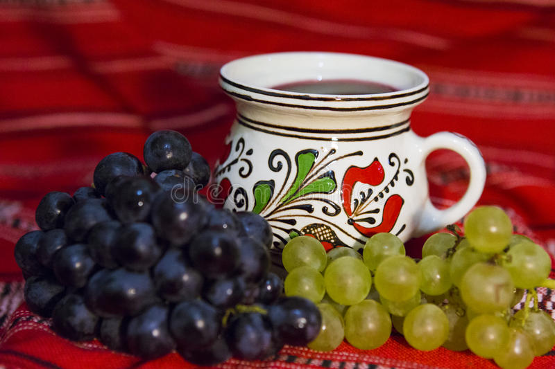 Grape and wine. Red and white grape and a mug of wine on a traditional Romanian carpet royalty free stock image