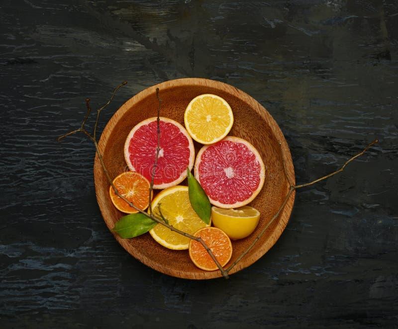 Grapefruit citrus fruit halves on wooden plate. Background stock images