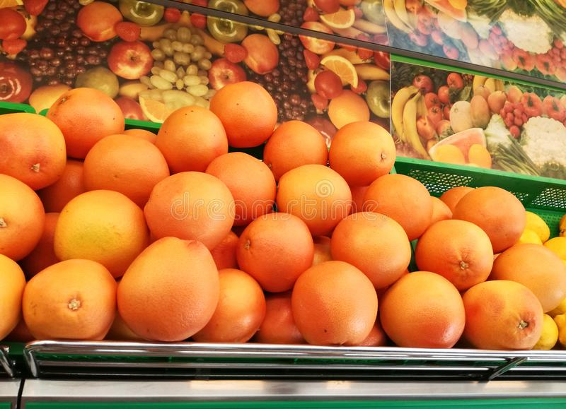 Grapefruit exhibited in the store in metal shelves. Orange fruits stock image
