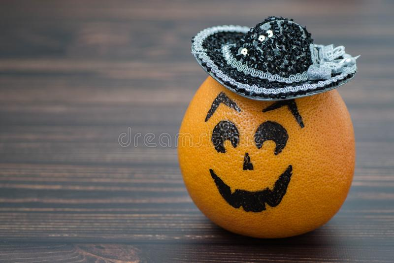 Grapefruit with a face drawn on it in the hat. Grapefruit with a face drawn on it in the hat on a wooden background. Photo on the theme of Halloween royalty free stock photos