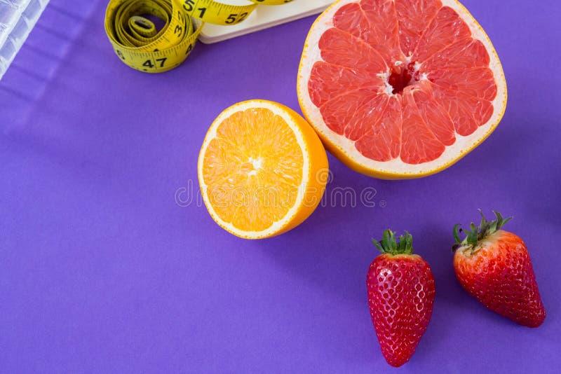 Grapefruit, lemon, strawberry with measuring tape royalty free stock photo