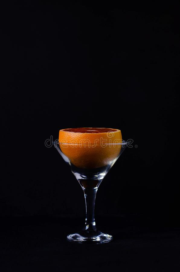 Grapefruit in a martini glass on a black background stock photo