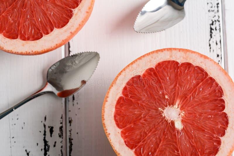 Grapefruit met lepel op witte houten achtergrond stock foto's