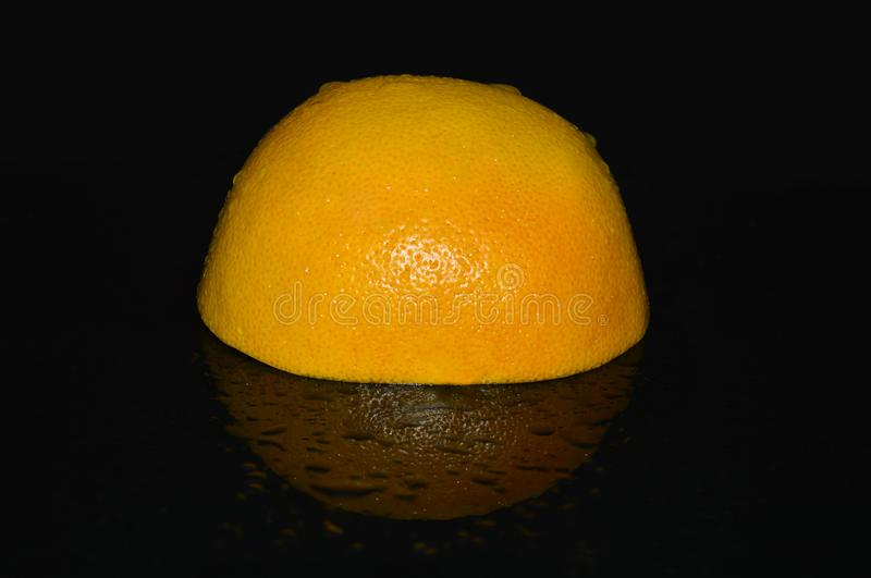 Grapefruit and orange on a black mirror background royalty free stock photo