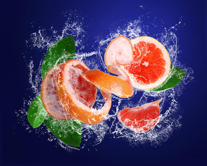 Grapefruit With Pieces And Leaves In Water Drops Royalty Free Stock Photo