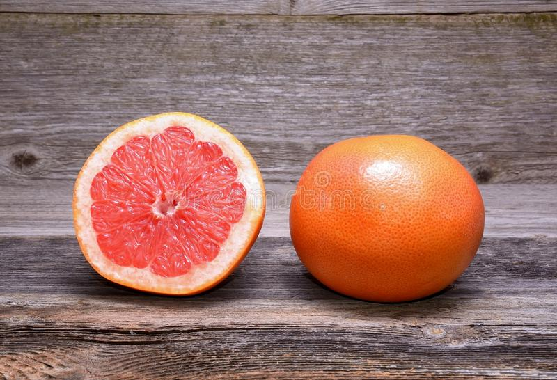Grapefruit with slices. On a wooden table royalty free stock photo