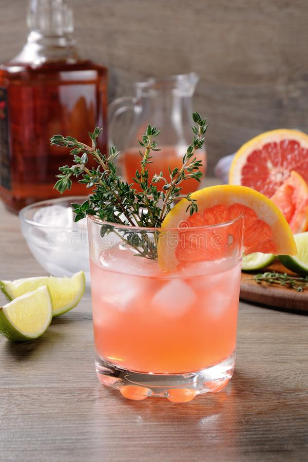 This Grapefruit and Thyme Bourbon. Muddled lime and thyme, combined with fresh grapefruit juice and delicious bourbon, it's the perfect way to get the royalty free stock photo