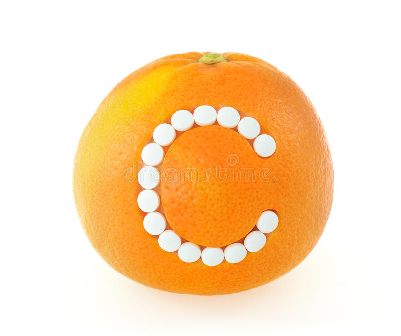 Grapefruit with vitamin c pills over white backgro. Und - concept stock photography