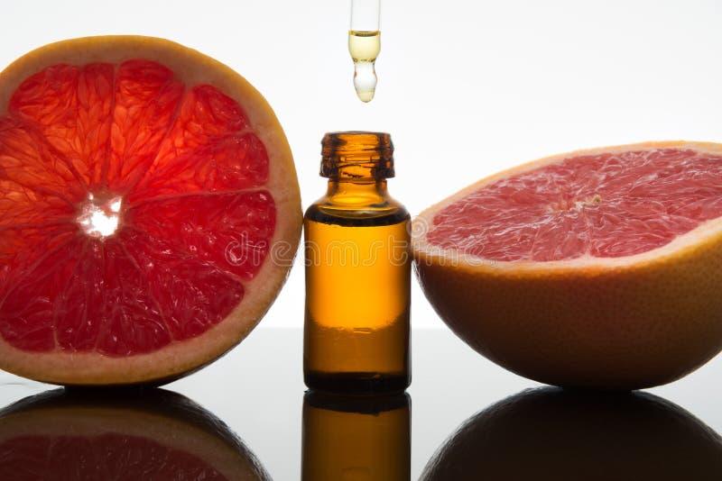 Grapefruitkernöl, Auszug, Wesentliches, in der bernsteinfarbigen Flasche mit Tropfenzähler lizenzfreie stockfotografie