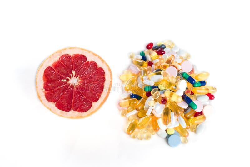 Grapefruitowy i pigułko, witamina nadprogramy na białym tle z kopii przestrzenią, zdrowej diety pojęcie zdjęcia royalty free