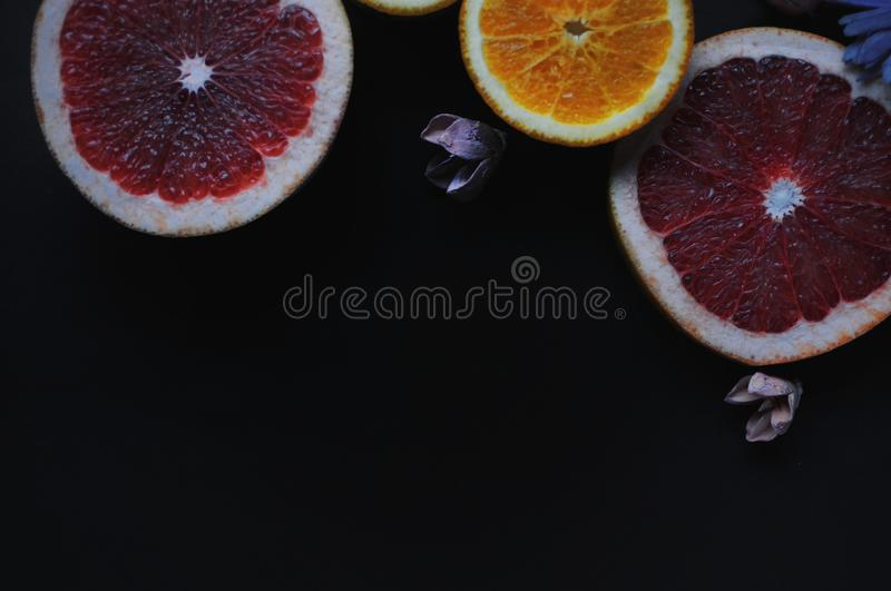 Grapefruits and oranges on black background. Fruits with flowers. Fruits wallpaper. Fruit slices royalty free stock image