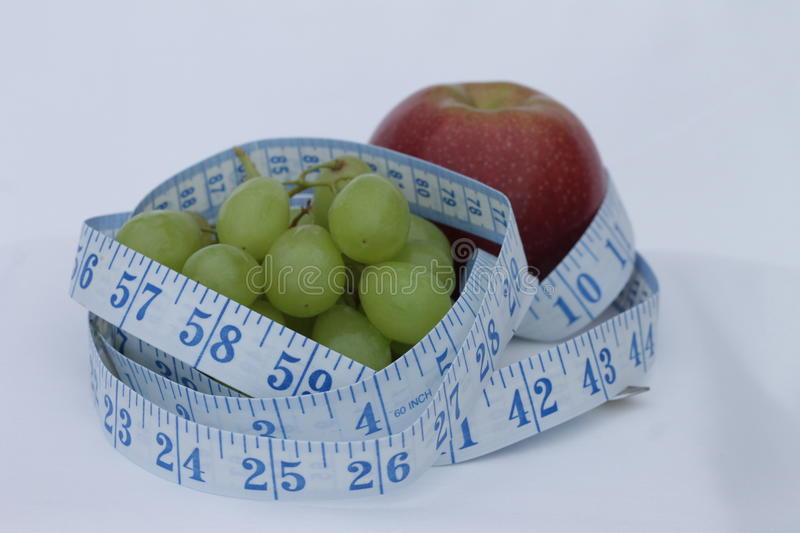 Grapes, Apple and tape Measure stock photography