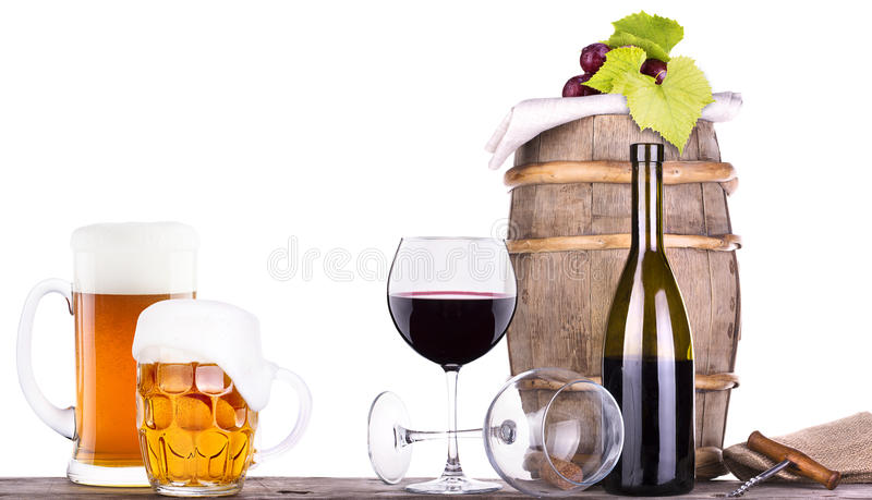 Grapes on a barrel with corkscrew and beer glass. Grapes on a wooden vintage barrel with corkscrew and beer glass isolated on a white background royalty free stock photo