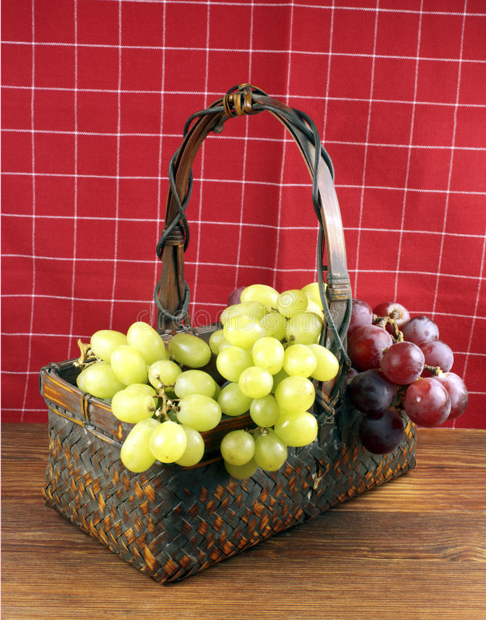 Grapes in a basket. Green and red grapes in a basket on a table stock photography