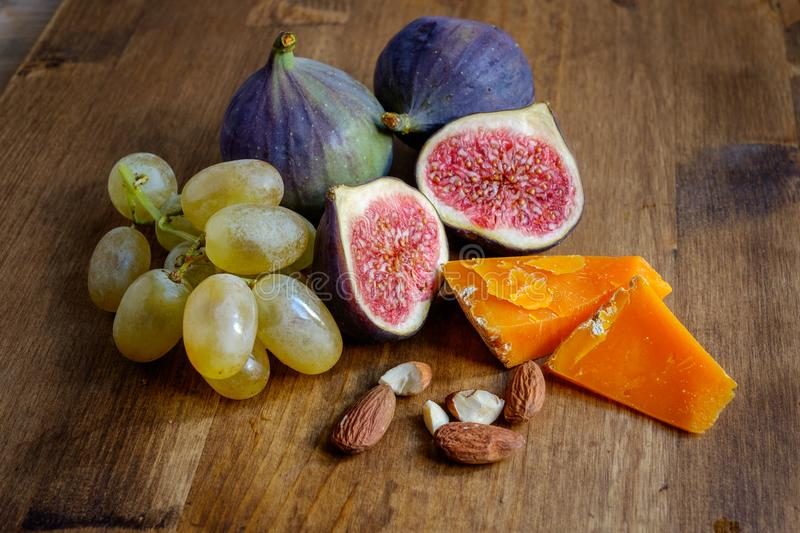 Grapes, figs, almonds and cheese in a bunch stock images