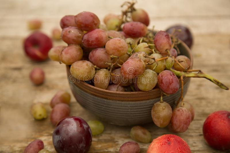 Grapes with grey plate on a wooden table stock images