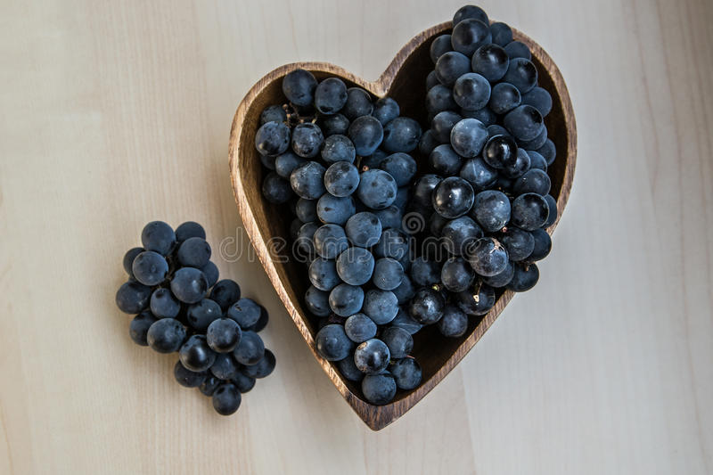 Grapes in a heart shape wooden plate stock images